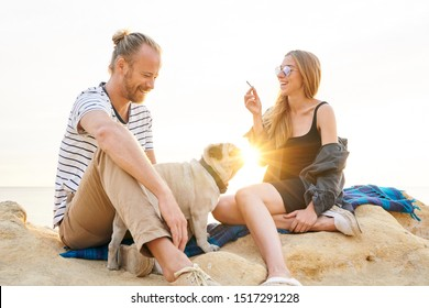 Happy couple with a dog smoking marijuana joint by the sea at sunset
