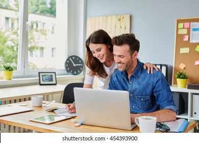 Happy couple doing business together working at small office on the laptop