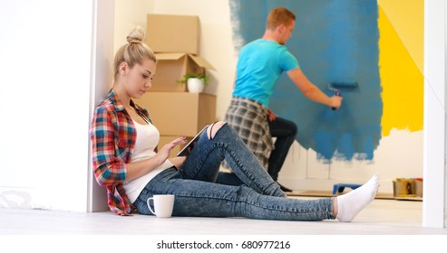 Happy couple doing home renovations, the man is painting the room and the woman is relaxing on the floor and connecting with a tablet