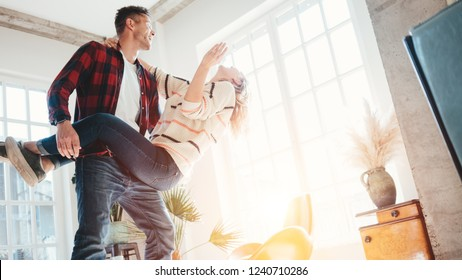 Happy couple domestic life situation. Wife and husband dancing together in big loft space