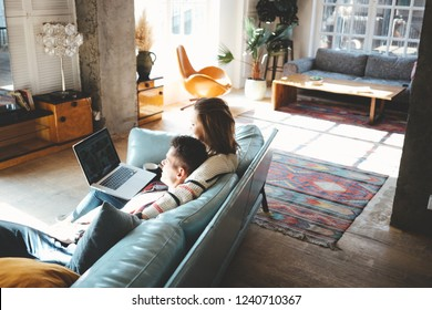 Happy couple domestic life situation. Husband and wife in love together watching laptop on sofa