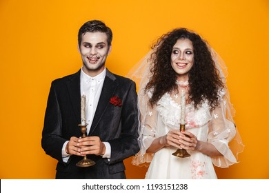 Happy couple dressed in scary Haloween costumes standing isolated over yellow background