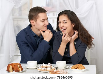 happy couple drinking coffee and having fun near window with a street view - travel and love concept