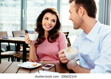 Happy couple drinking coffee and talking in a canteen
