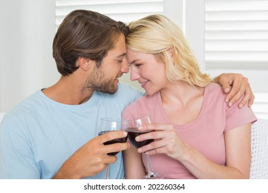 Happy couple drinking red wine together on the couch at home in the living room
