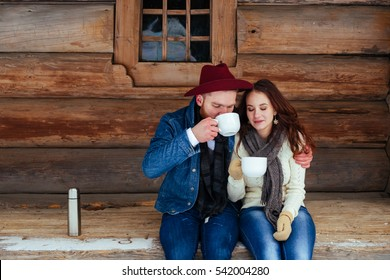 Happy couple drinking tea and wood old house