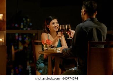 Happy couple drinking wine when having date in restaurant