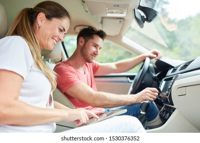 Happy couple driving in car using tablet computer as navigation system