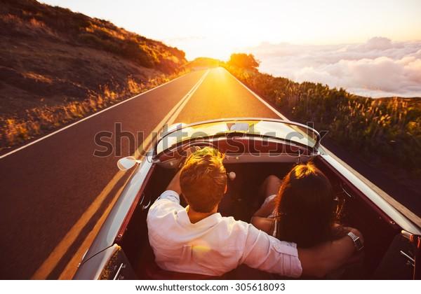 Happy Couple Fahren auf der Landstraße in den Sonnenuntergang im klassischen Vintage Sports Car