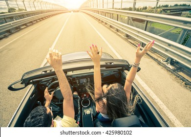 Happy couple driving on the road into the sunset in a sports car