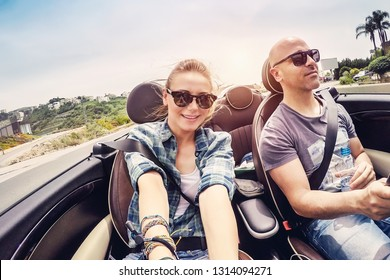 Happy couple driving open car and making selfie, honeymoon vacation in convertible auto, soul mates enjoying road trip, enjoying summer