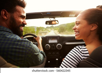 Happy couple driving in their car looking at each other