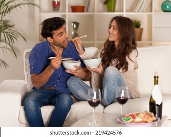 Happy couple eating chinese food and drinking wine at home.