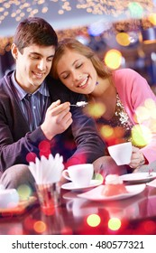 Happy couple eating dessert together in cafe