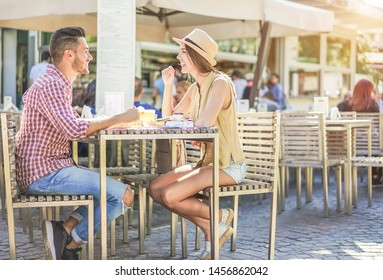 Happy couple eating and drinking beer in bar street food restaurant during summer vacation - Young people having fast meal sitting outdoor - Love and travel concept - Main focus on girl face