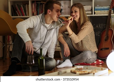 Happy couple eating pizza at home , in evening hours.