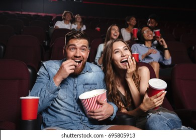 Happy couple eating popcorn and laughing while sitting and watching movie at the cinema