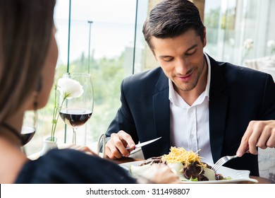 Happy couple eating in restaurant with a red wine