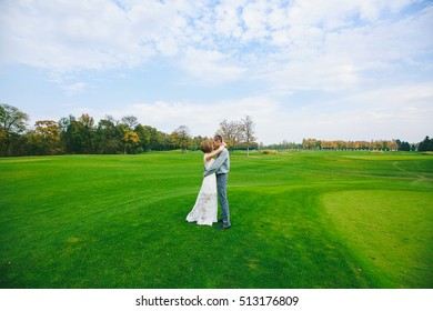 happy couple embrace on the field with green grass.