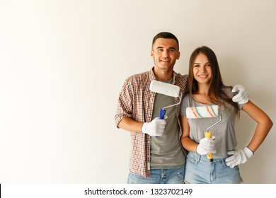 Happy couple embracing after renovation their new home together with paint roller