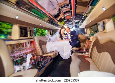Happy couple embracing in limousine on wedding-day