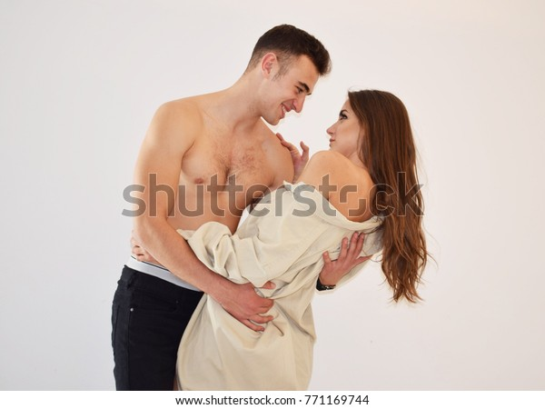 Happy couple embracing and looking at each other on white background