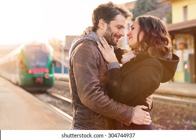 Happy couple embracing on railway station platform