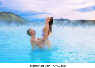 A happy couple enjoy the blue lagoon spa resort in Iceland, the man holds the woman and uplift her in front of himself