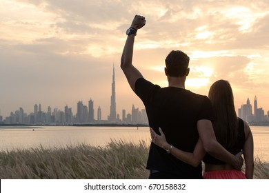 Happy couple enjoying the beautiful Dubai city view during sunset.
