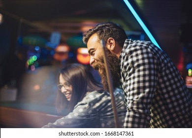 happy couple enjoying in a billiard game
