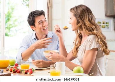 Happy Couple Enjoying Breakfast In Kitchen