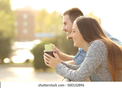 Happy couple enjoying breakfast and looking away in a balcony with an urban background with a warm light at sunset