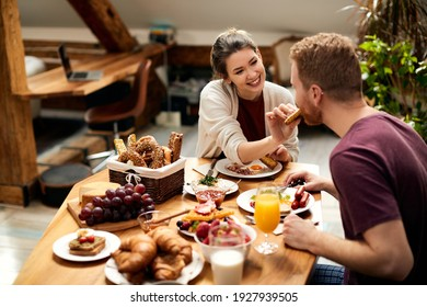 Happy couple enjoying in breakfast together at home. Focus is on woman feeding her boyfriend.