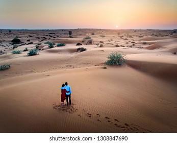 Happy couple enjoying desert sunset aerial view