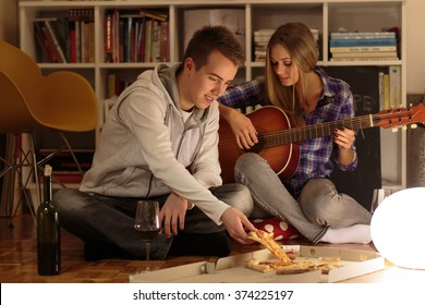 Happy couple enjoying evening together at home. having pizza and wine for dinner.