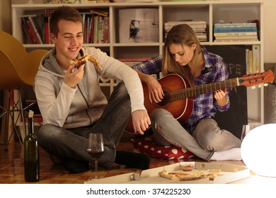 Happy couple enjoying evening together at home. man eating pizza.