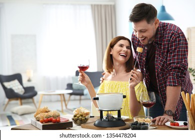 Happy couple enjoying fondue dinner at home