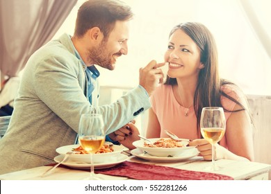Happy couple enjoying food in an Italian restaurant. Love concept.