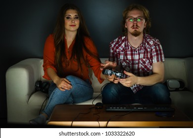 Happy couple enjoying leisure time by playing video games together. Studio shot