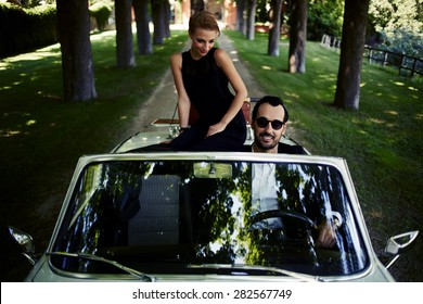 Happy couple enjoying a ride on their luxury convertible in the summer,gorgeous rich woman feels so glad while they riding on cabriolet with sure handsome brunette man, romantic couple at journey trip