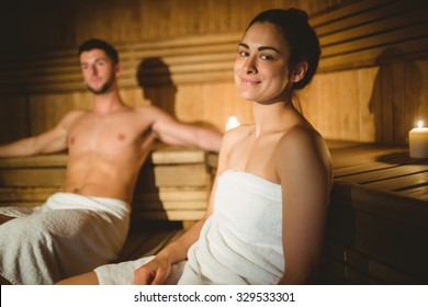 Happy couple enjoying the sauna together at the spa