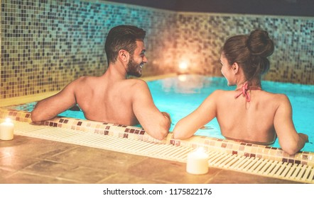 Happy couple enjoying spa swimming pool with candles and soft lights - Young people doing romantic vacation in resort hotel - Relationship, holidays and love concept - Focus on woman head
