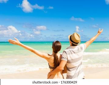 Happy couple enjoying summer beach. Freedom concept.