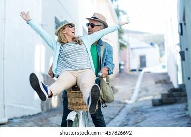 Happy couple enjoying while riding bicycle on street