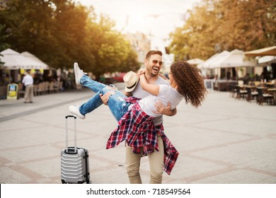 Happy couple enjoys at streets of the city. He is holding her spinning around. Find your travel partner.
