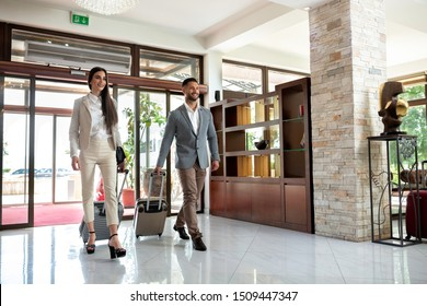 Happy couple entering the hotel pulling their luggage, vacation concept