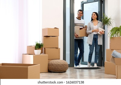 Happy couple entering their new flat with moving boxes