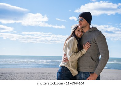 Happy couple enyojing time together on beach during autumn day