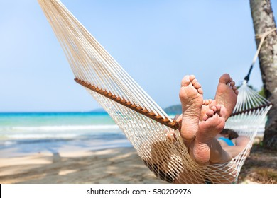 happy couple family in hammock on tropical paradise beach, island holidays, closeup of feet