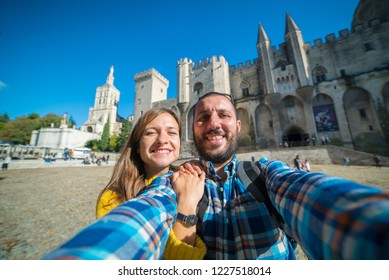Happy couple family take photo selfie in Avignon in front of the Popes Palace, Saint-Benezet. Provence, France